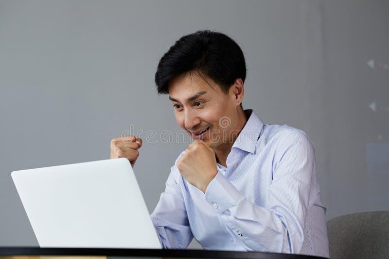 Hombre asiático joven emocionado feliz con el ordenador portátil en casa que se sienta en la tabla imagenes de archivo