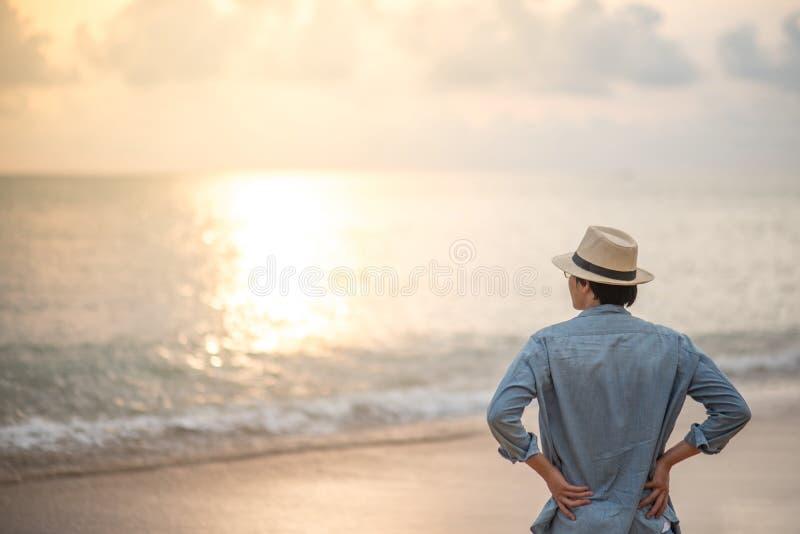 Hombre asiático joven en la playa que mira puesta del sol hermosa foto de archivo