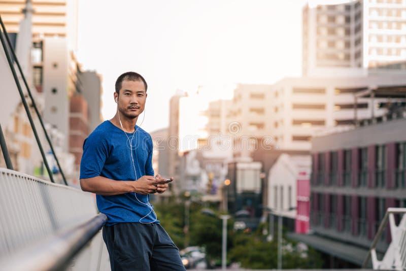 Hombre asiático joven que escucha la música antes de un funcionamiento de la ciudad fotos de archivo