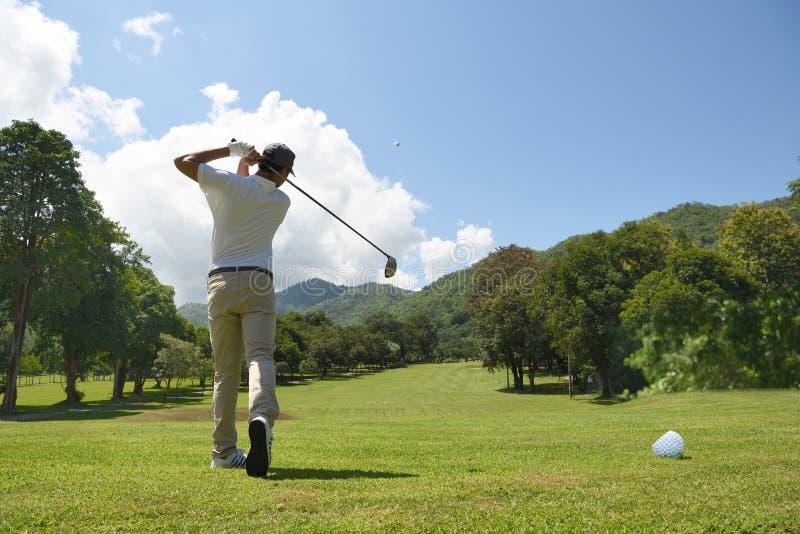 Hombre asiático joven que juega a golf fotografía de archivo