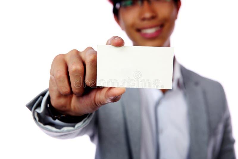 Hombre asiático joven que muestra la tarjeta vacía fotografía de archivo