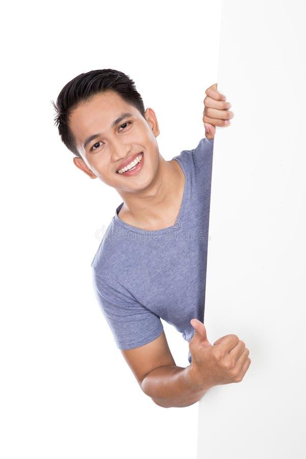 Hombre asiático joven que sostiene una bandera en blanco que muestra el pulgar para arriba imagen de archivo
