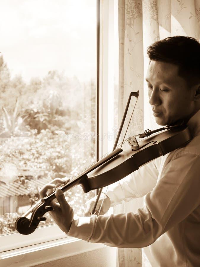 Hombre asiático joven que toca el violín Instrumento de música clásica Tono del color de la sepia foto de archivo