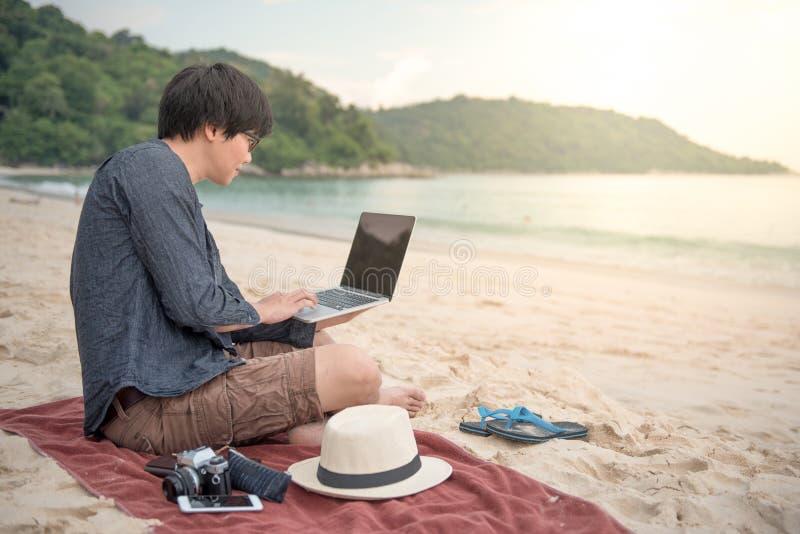 Hombre asiático joven que trabaja con el ordenador portátil en la playa imagenes de archivo
