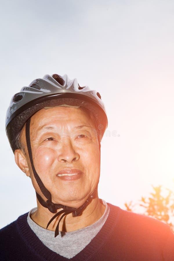 Hombre asiático mayor con el casco de la bici fotografía de archivo