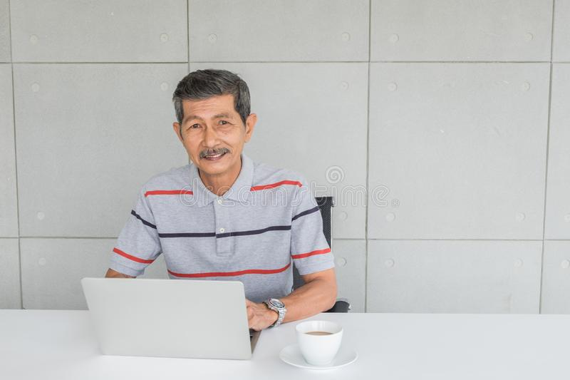 Hombre asi?tico mayor feliz, sonriendo frente en el escritorio hay ordenador port?til con la taza del caf? con leche foto de archivo