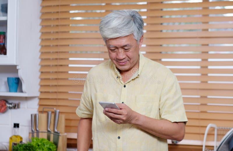 Hombre asiático mayor usando el teléfono elegante mientras que se coloca en cocina en casa, gente y tecnología imagenes de archivo