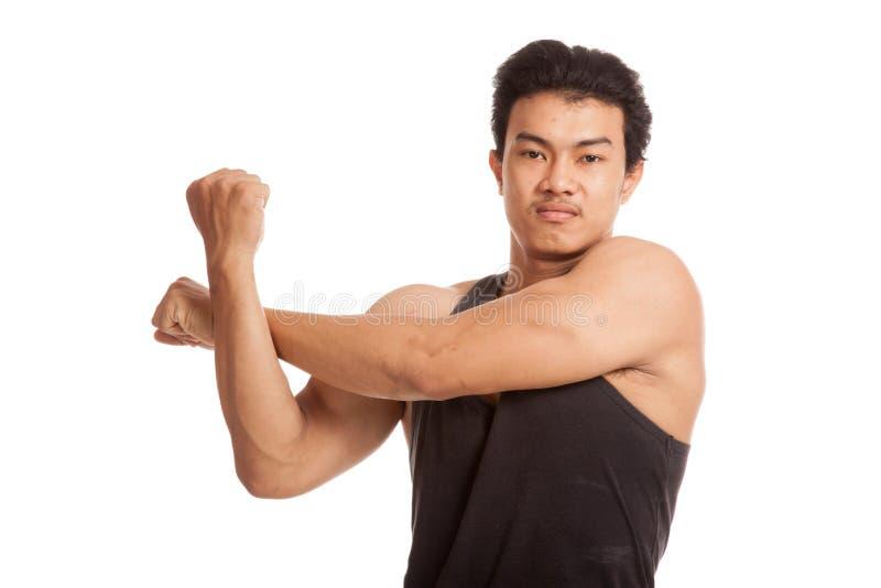 Hombre asiático muscular que estira su brazo imágenes de archivo libres de regalías