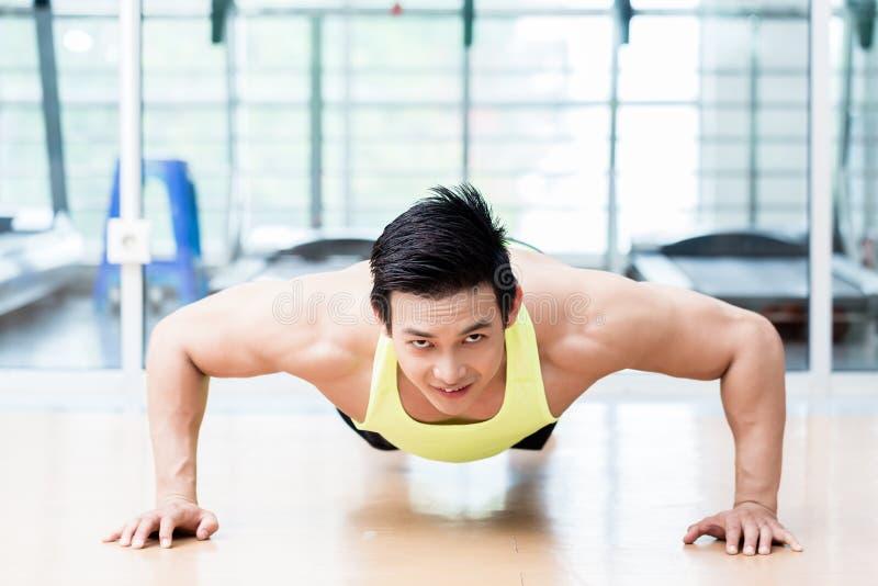 Hombre asiático muscular que hace flexiones de brazos en gimnasio imagenes de archivo