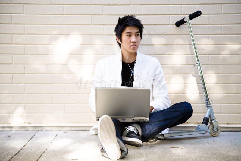 Hombre asiático ocasional joven con la computadora portátil foto de archivo
