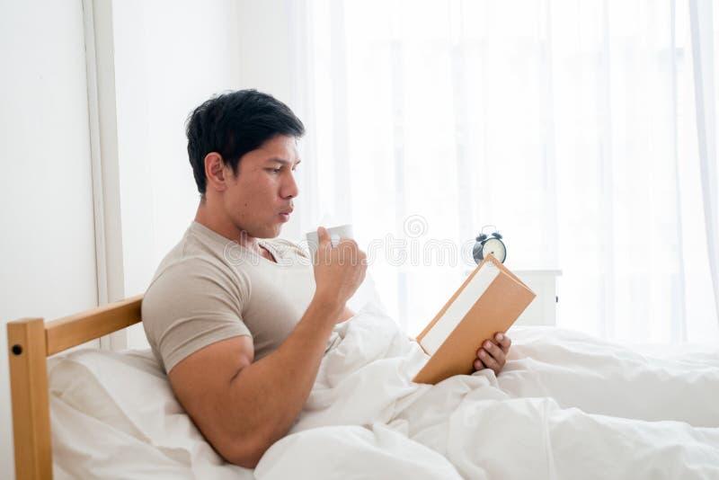 Hombre asiático que bebe una taza de café o de desayuno en cama fotografía de archivo