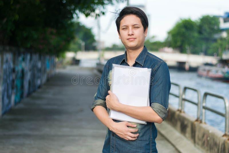 Hombre asiático que coloca y que sostiene el fichero de documento fotos de archivo libres de regalías