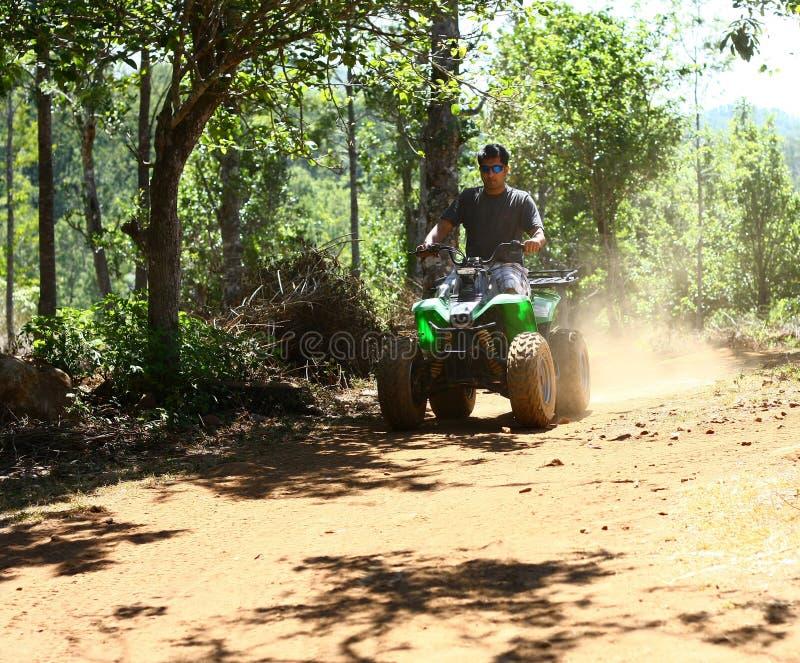 Hombre Asiático Que Conduce El Vehículo Todo Terreno En Selva Foto de archivo