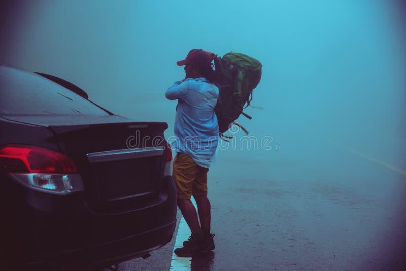 Hombre asiático que conduce un coche que viaja para relajar la naturaleza Naturaleza que viaja en medio de la niebla lluviosa en  fotos de archivo