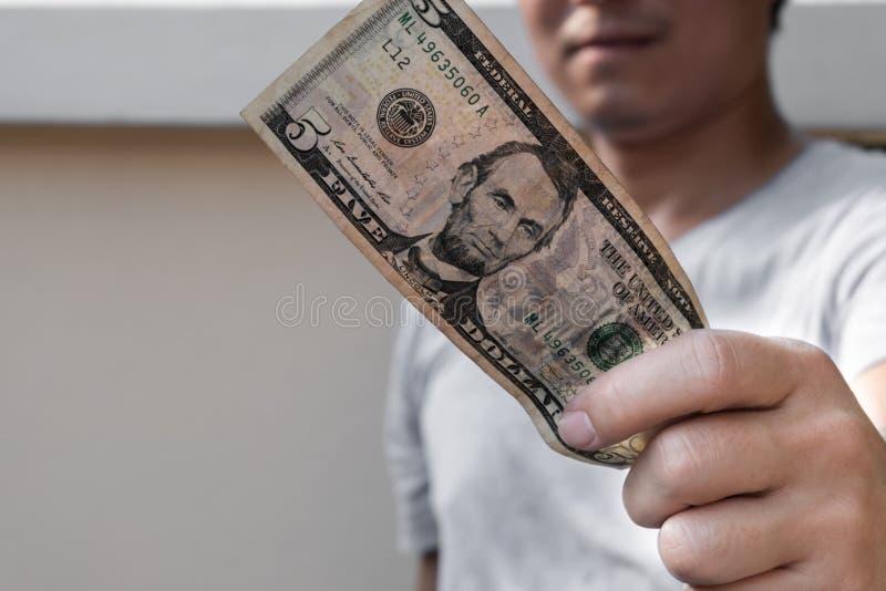 Hombre asiático que lleva a cabo el billete de dólar cinco r imagenes de archivo