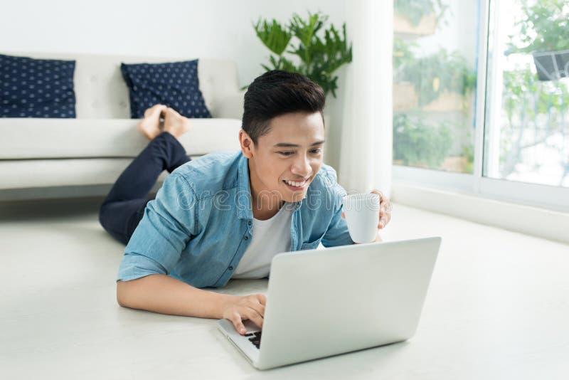 Hombre asiático que miente en el piso con el ordenador portátil y el café fotografía de archivo