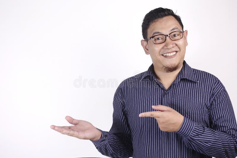 Hombre asiático que presenta algo en su lado con el espacio de la copia foto de archivo
