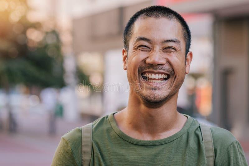 Hombre asiático que ríe mientras que se coloca en una calle de la ciudad imagenes de archivo
