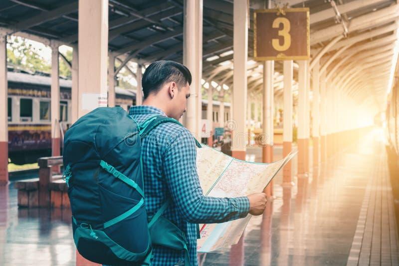 Hombre asiático que se coloca en la plataforma y que sostiene el mapa con el plac del hallazgo imagenes de archivo