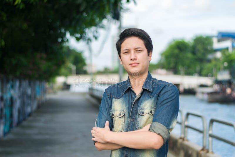 Hombre asiático que se coloca y que muestra la cara lisa foto de archivo