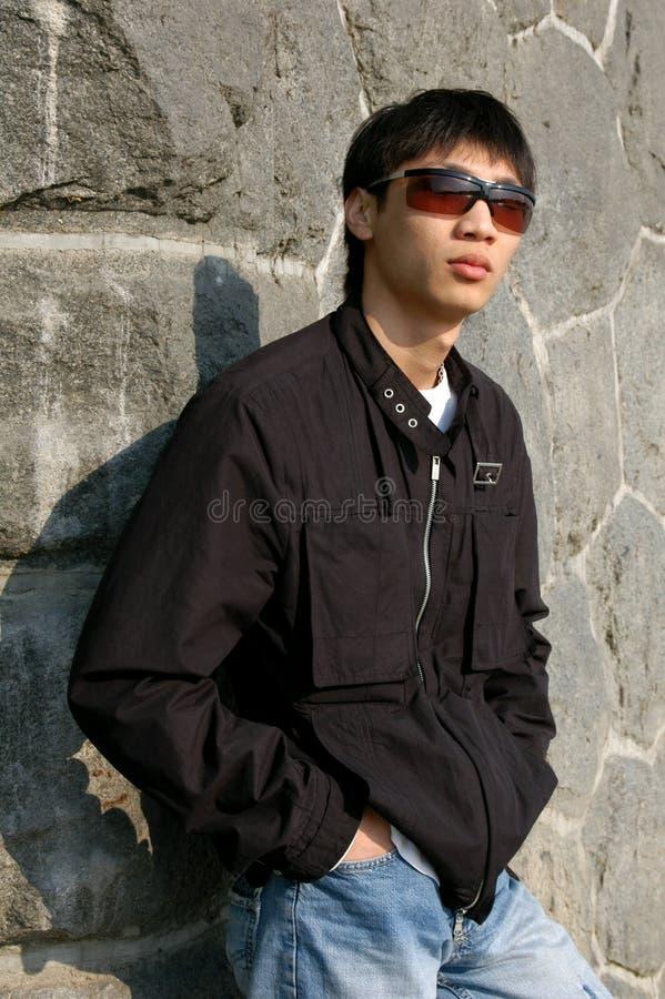 Hombre asiático que se inclina contra una pared fotos de archivo