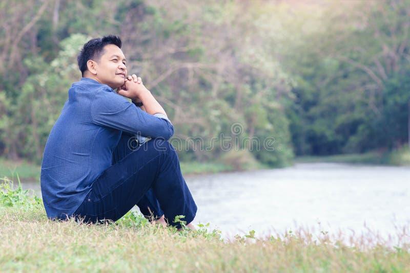 Hombre asiático que se sienta en la tierra en la naturaleza foto de archivo libre de regalías