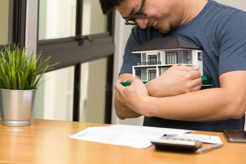 Hombre asiático que sonríe y que abraza un hogar ideal y calcular para comprar una casa que sueña en su futuro, imagenes de archivo