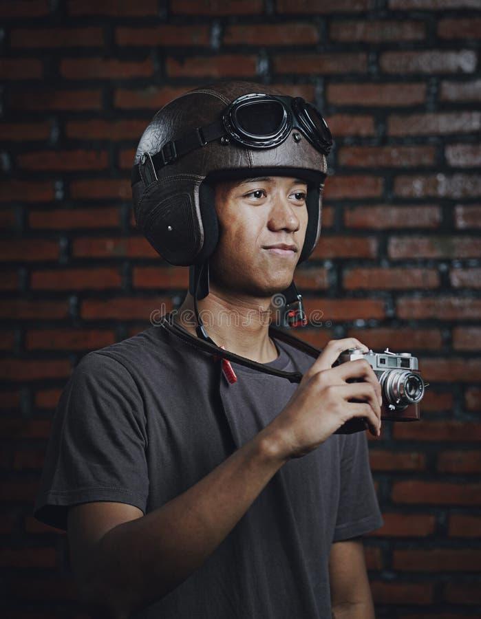 Hombre asiático que sostiene la cámara del vintage que lleva el casco retro foto de archivo libre de regalías
