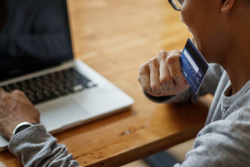 Hombre asiático que sostiene la tarjeta de crédito y que usa el ordenador portátil mientras que se sienta en café Concepto en lín foto de archivo libre de regalías