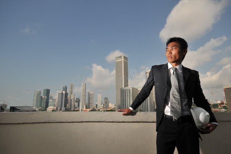 Hombre asiático que sostiene un sombrero duro imagenes de archivo