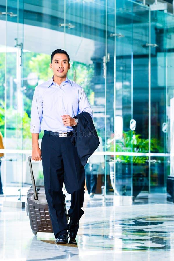 Hombre asiático que tira de la maleta en pasillo del hotel fotos de archivo libres de regalías