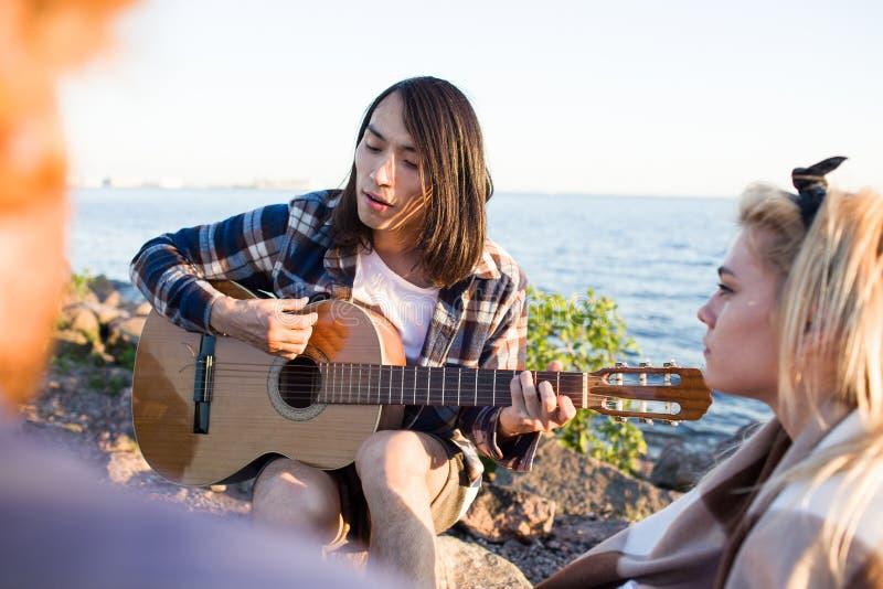 Hombre asiático que toca la guitarra durante partido fotografía de archivo libre de regalías