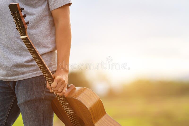 Hombre asiático que toca la guitarra en el campo verde del arroz en el tiempo de la puesta del sol imagenes de archivo