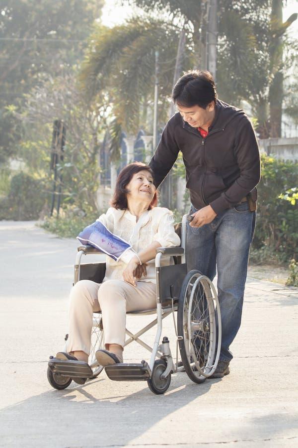 Hombre asiático que toma a su madre mayor para un paseo foto de archivo libre de regalías
