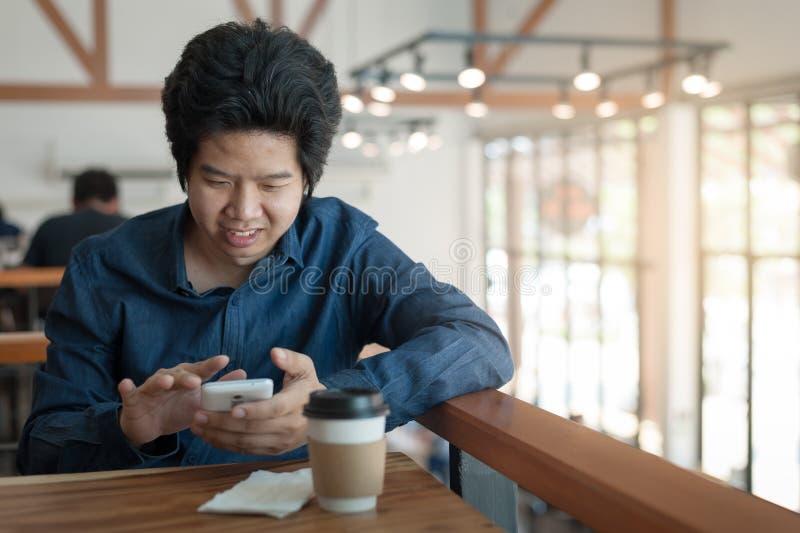 Hombre asiático que usa el teléfono en cafetería fotografía de archivo