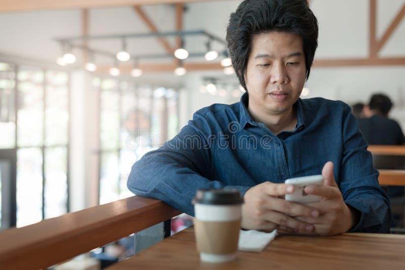Hombre asiático que usa el teléfono en cafetería fotografía de archivo libre de regalías