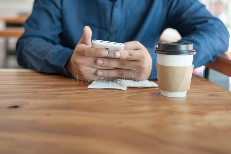 Hombre asiático que usa el teléfono en cafetería imagenes de archivo
