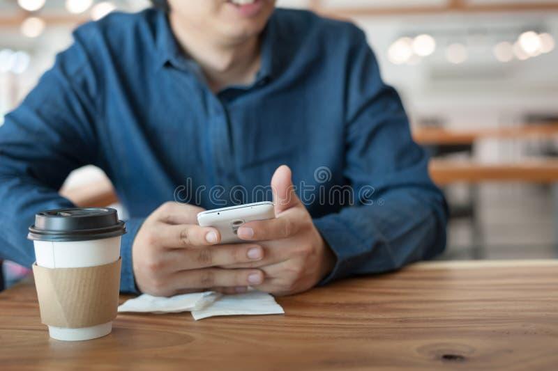 Hombre asiático que usa el teléfono en cafetería imágenes de archivo libres de regalías