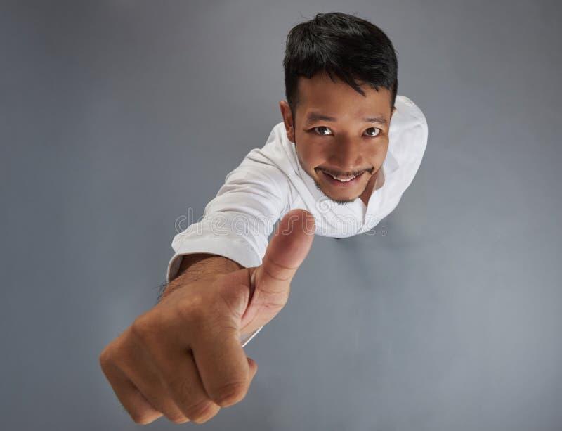 Hombre asiático sonriente con el pulgar para arriba imágenes de archivo libres de regalías