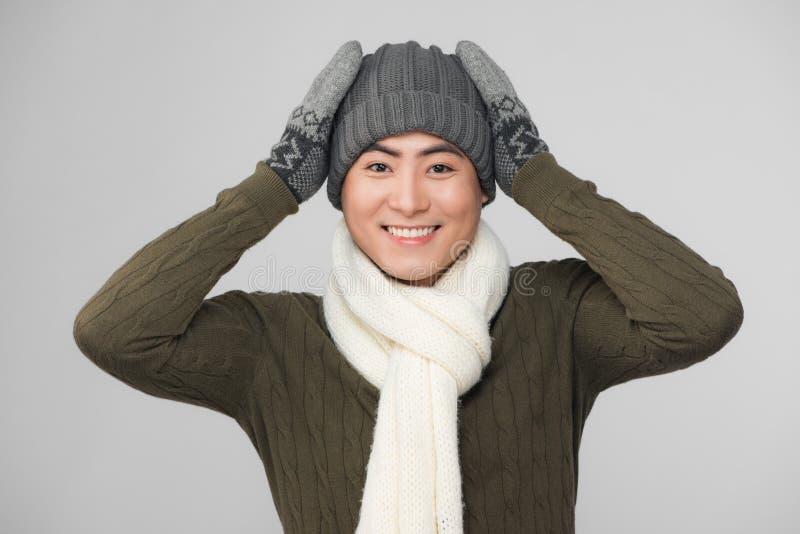 Hombre asiático sonriente de los jóvenes que lleva el suéter y guantes hechos punto fotografía de archivo