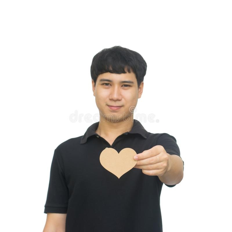 Hombre asiático sonriente joven que sostiene la tarjeta marrón en blanco de la forma del corazón imagenes de archivo