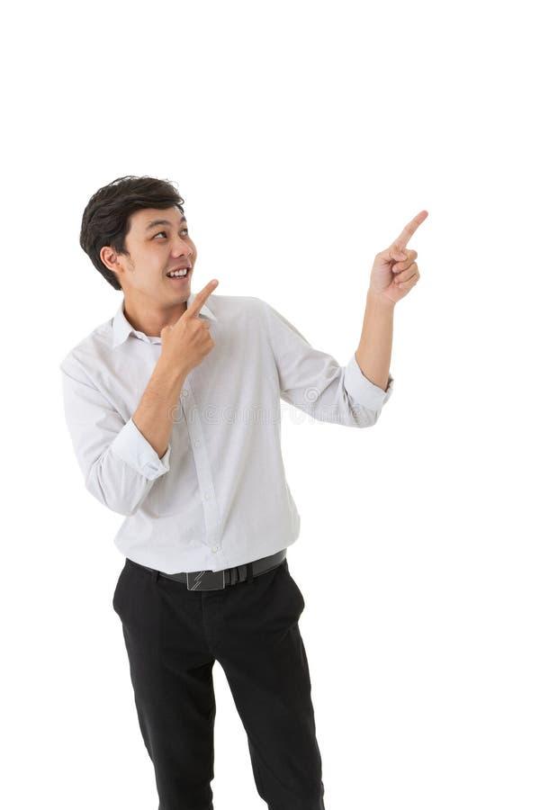 Hombre asiático sonriente que mira y el señalar aislado en el fondo blanco fotografía de archivo