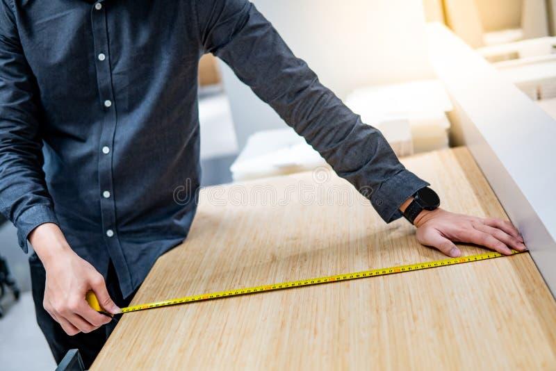 Hombre asiático usando cinta métrica en encimera fotografía de archivo libre de regalías