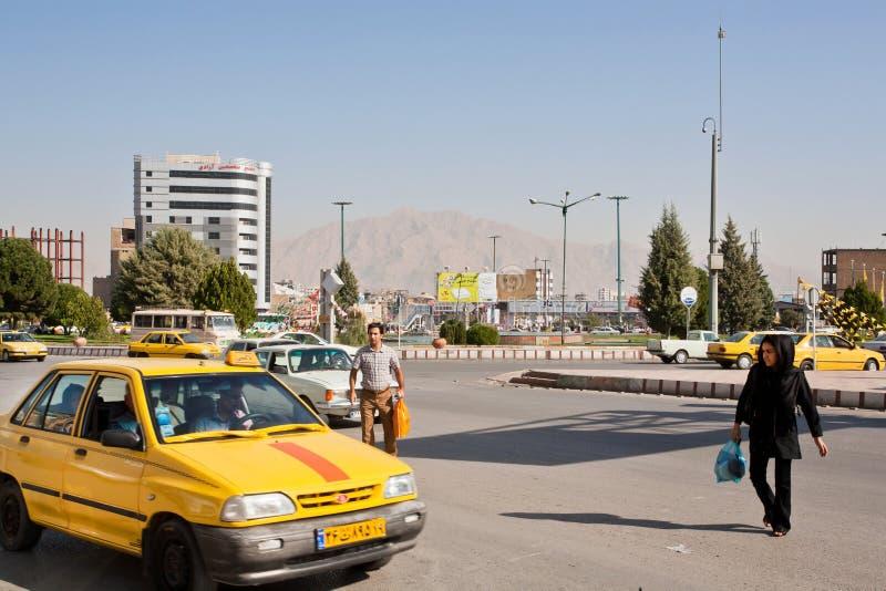 Hombre asiático y mujer que intentan coger el taxi en el camino ocupado fotografía de archivo