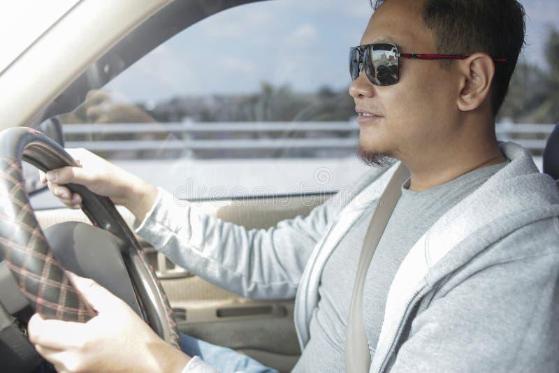 Hombre asi?tico joven que conduce un coche imagenes de archivo