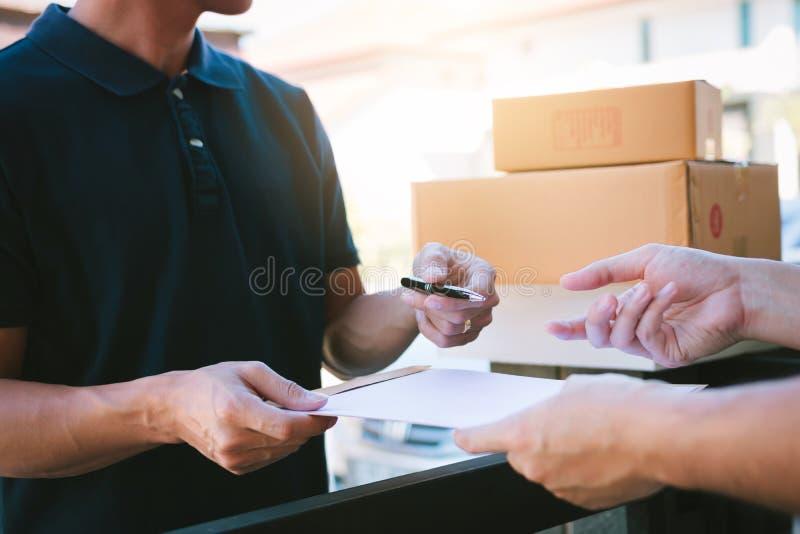 Hombre asi?tico joven que sonr?e mientras que entrega una caja de cart?n al documento de la tenencia de la mujer a la firma de fi foto de archivo