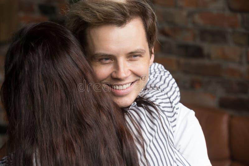 Hombre astuto joven del mentiroso que sonríe feliz mientras que mujer que lo abraza fotografía de archivo