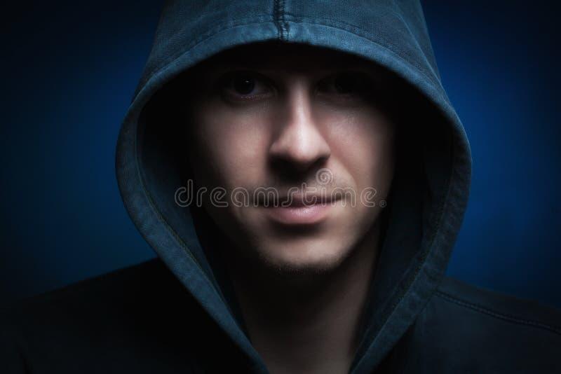 Hombre asustadizo con el capo motor en oscuridad fotografía de archivo libre de regalías