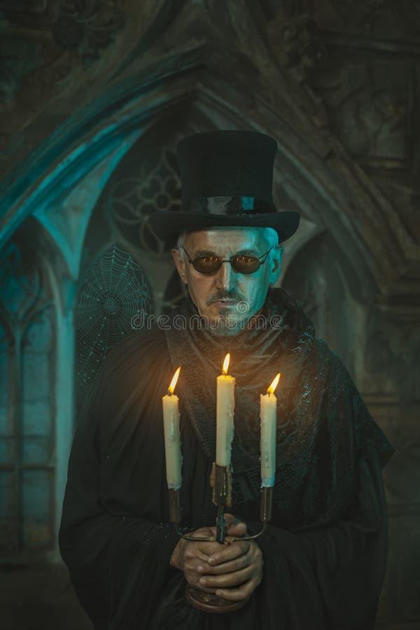 Hombre asustadizo con las velas en los candelabros imágenes de archivo libres de regalías