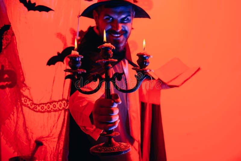 Hombre asustadizo de la cara con el horror Make up que celebra la linterna del enchufe de la cabeza de la calabaza en fondo del c fotografía de archivo libre de regalías